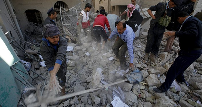 Policemen and medics remove debris as they search for victims at the site of a Saudi-led air strike on the police headquarters in Yemen's capital Sanaa, January 18, 2016