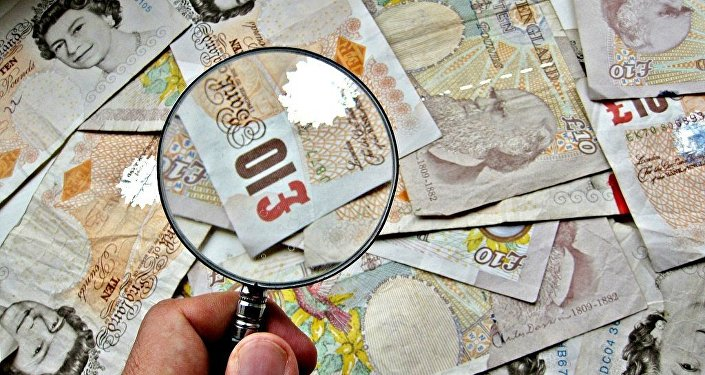 A pile of £10 notes with a magnifying glass