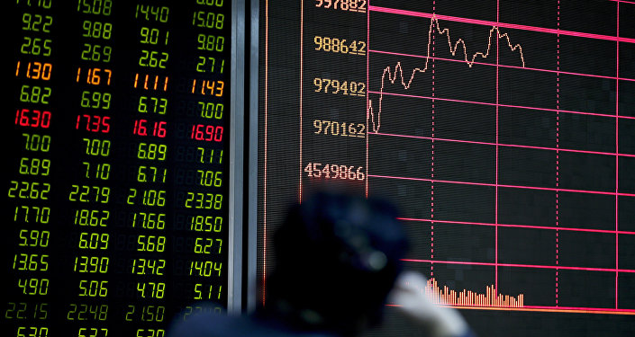 An investor looks at an electronic board displaying stock prices at a brokerage house in Beijing, Thursday, Jan. 14, 2016