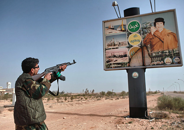 An armed supporter of the Libyan opposition shoots a machine gun at a poster with the image of Muhammar Gaddafi in the captured rebel town of Ras-Lanuf in the east of the country
