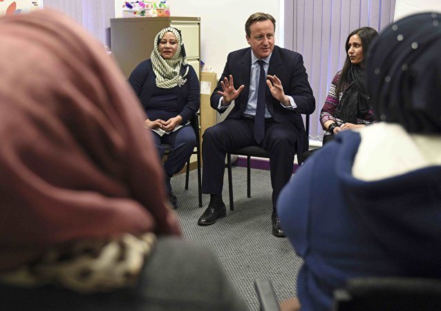 Britain's Prime Minister David Cameron speaks with women attending an English language class during a visit to the Shantona Women's Centre in Leeds, Britain January 18, 2016.