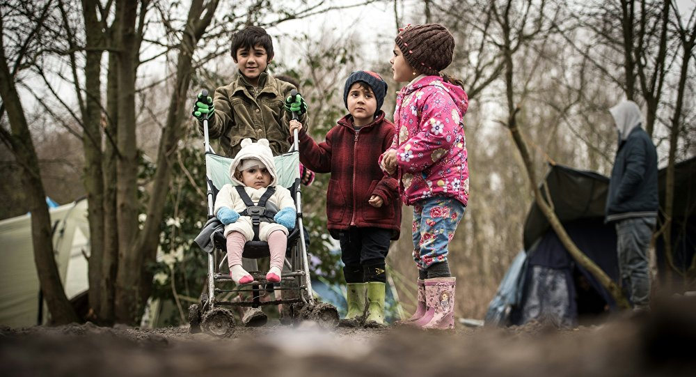 Young migrants or refugees walk with a stroller on December 29, 2015 in a camp in Grande-Synthe.