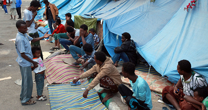 African migrants sit outside tents at a makeshift shelter on June 19, 2014, in the Yemeni capital Sanaa