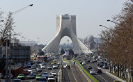 A picture taken on January 18, 2016 shows vehicles driving on a street in front of the Azadi Tower in the capital Tehran