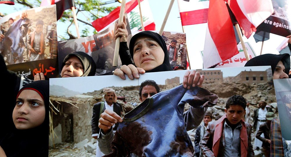 Women and children hold up Yemeni and Lebanese flags and placards