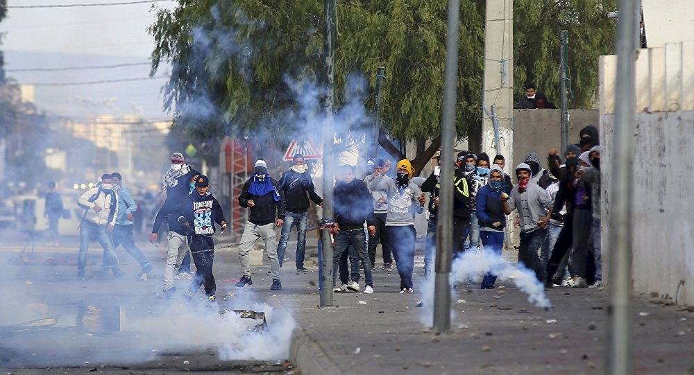 Protesters throwing rocks are seen amid tear gas fired by police in Kasserine, Tunisia