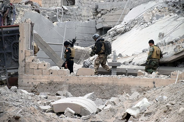 Iraqi security forces, supported by US-led coalition airstrikes, advance their position through damaged buildings towards the central Ramadi, 70 miles (115 kilometers) west of Baghdad, Iraq, Thursday, December 24, 2015.