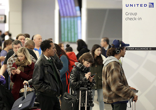 Travelers wait to be ticketed at the United airlines booth