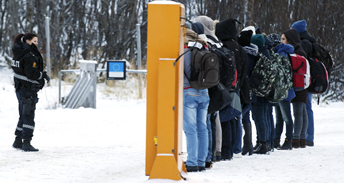 Migrants receive instructions from a Norwegian police officer at Storskog border crossing station