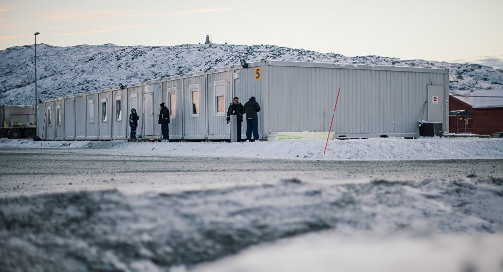 Refugees stand in front of residential containers at the arrival centre for refugees near the town on Kirkenes, northern Norway, close to the Russian - Norwegian border on November 12, 2015