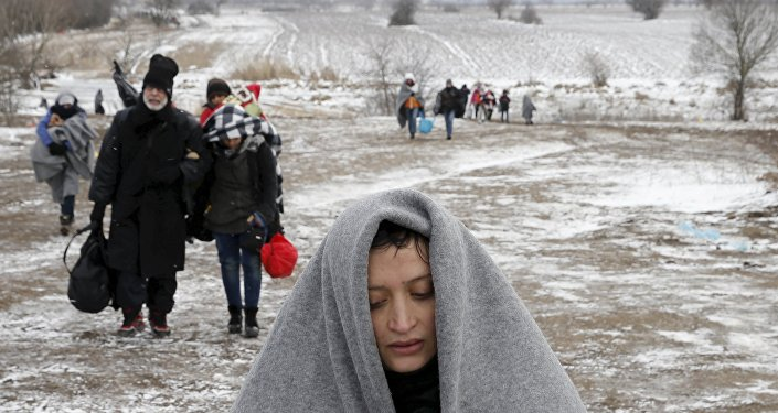 Migrants walk through a frozen field after crossing the border from Macedonia, near the village of Miratovac, Serbia, January 18, 2016.