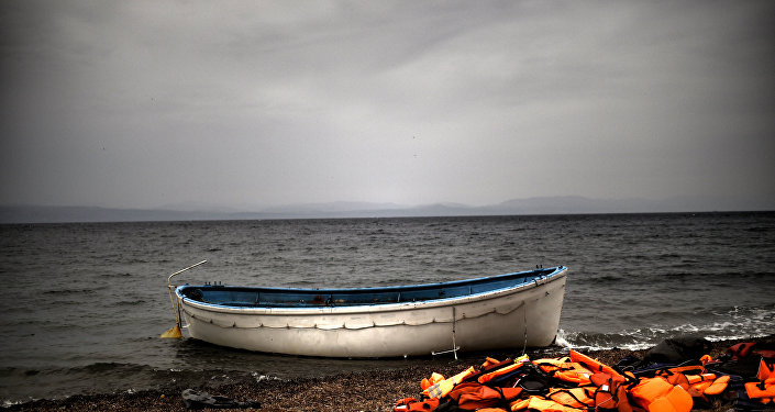 Life jackets and a boat that were used by refugees and migrants to cross the Aegean sea from Turkey lie abandoned on a beach on the Greek Island of Lesbos on October 8, 2015.