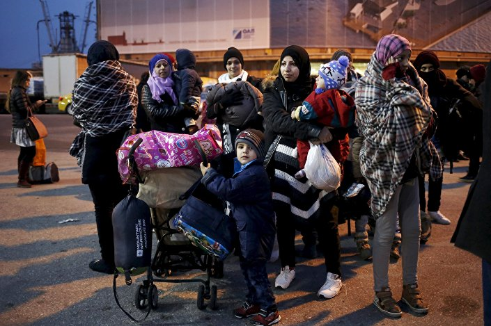 Refugees and migrants arrive aboard the passenger ferry Nissos Rodos at the port of Piraeus, near Athens, Greece, January 27, 2016.