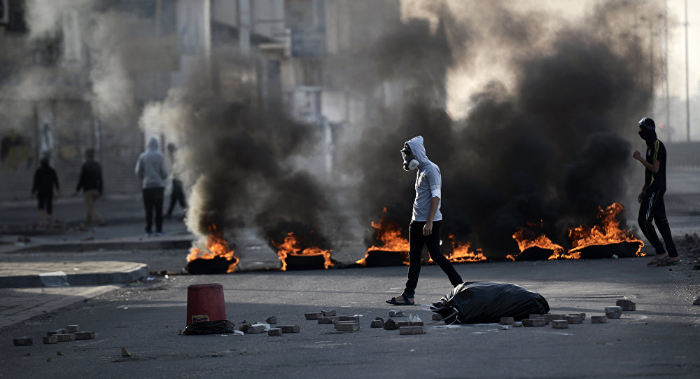 Bahraini protesters walk past burning tyres during clashes with riot police in the village of Sitra, south of the capital Manama, on January 8, 2016, following a protest against the execution of prominent Shiite Muslim cleric Nimr al-Nimr by Saudi authorities