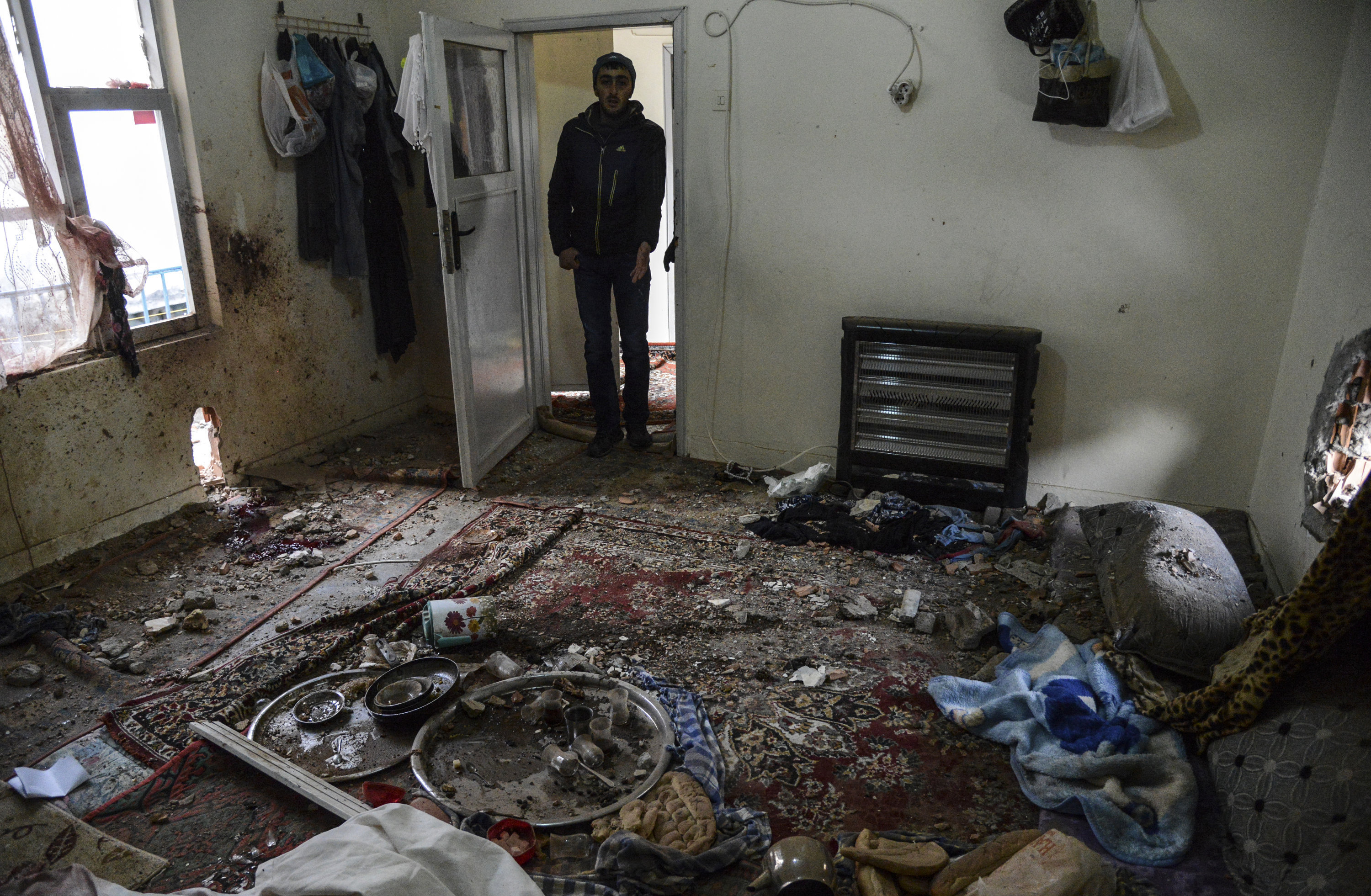A man stands in the room of a house after it was hit by a mortar during clashes with Turkish police at the Sur district in Diyarbakir, southeastern Turkey, on January 3, 2016
