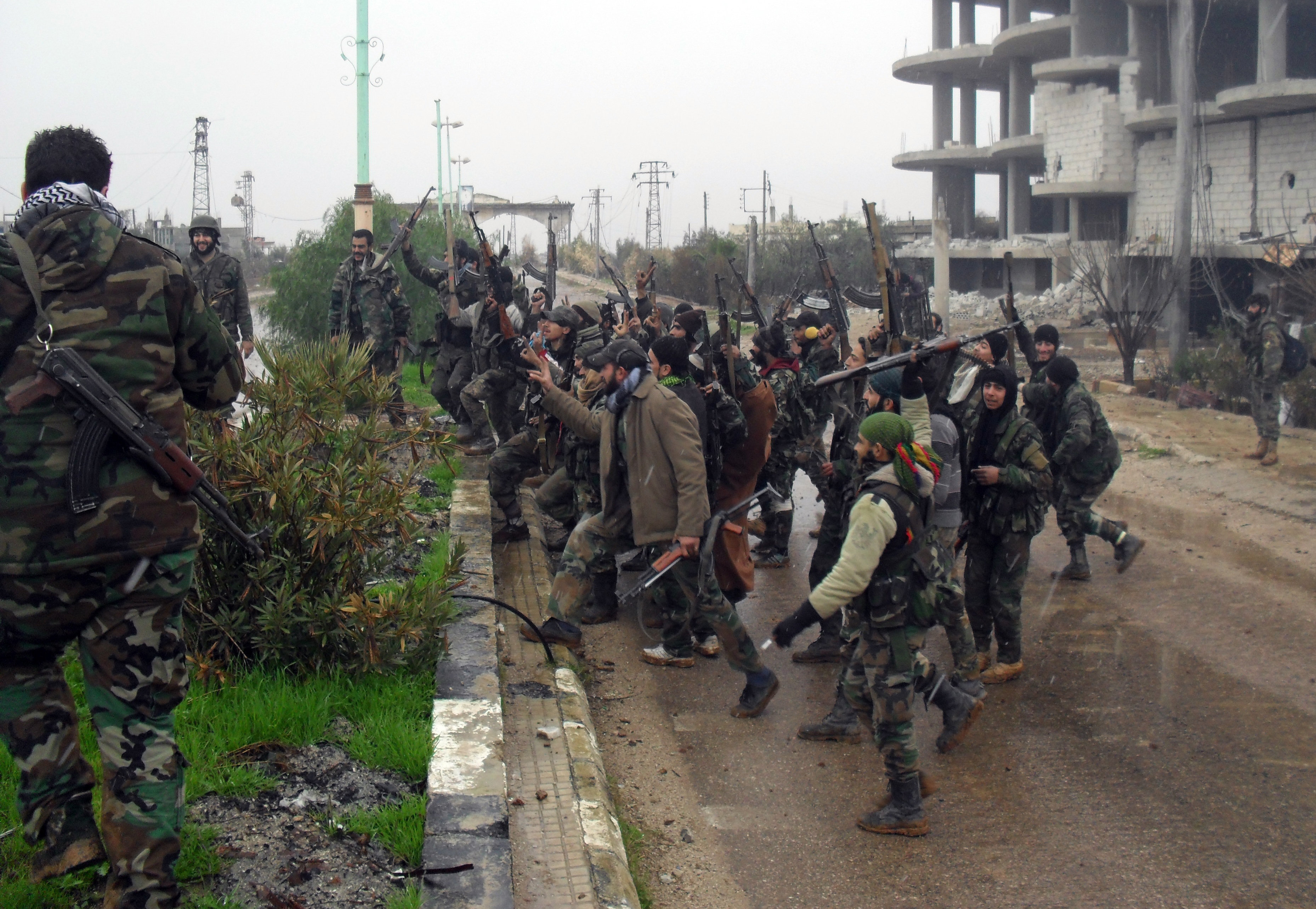 Syrian pro-government forces celebrate on a street in the town of Sheikh Miskeen in southern Daraa province on January 26, 2016 after they retook the strategic town from terrorists