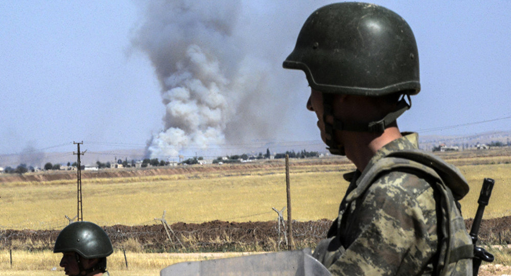 Turkish soldiers stand guard by the border with Syria