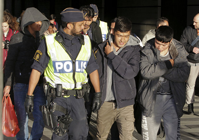 A group of migrants off an incoming train walk down a platform as they are accompanied by the police at the Swedish end of the bridge between Sweden and Denmark near Malmoe on November 12, 2015