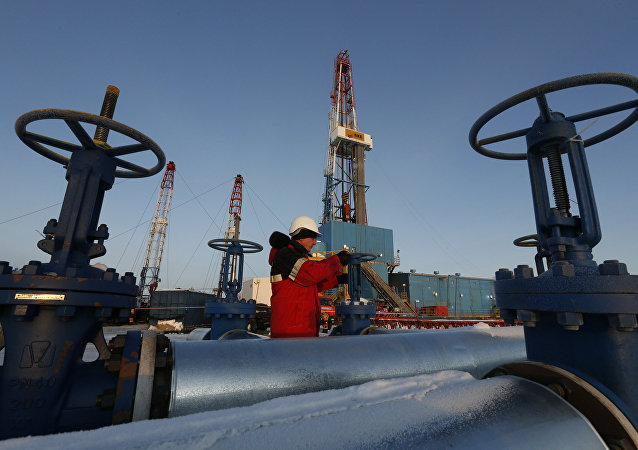 A worker checks a valve of an oil pipe at the Lukoil company owned Imilorskoye oil field outside the West Siberian city of Kogalym, Russia, January 25, 2016