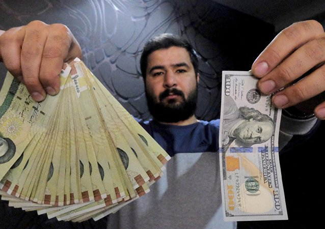 A money changer poses for the camera with a US dollar (R) and the amount being given when converting it into Iranian rials (L), at a currency exchange shop in Tehran's business district, Iran, in this January 20, 2016 file photo