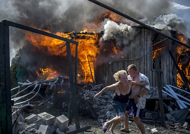 Local residents escape from a fire in the house destroyed in the Ukrainian armed forces' air attack on the village of Luganskaya