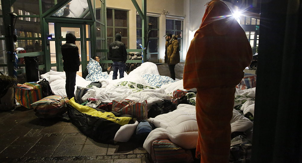 Refugees sleep outside the entrance of the Swedish Migration Agency's arrival center for asylum seekers