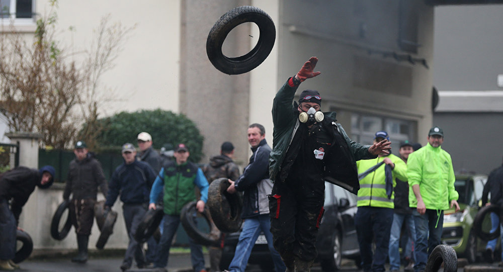 Protesting farmers throw tyres during clashes with riot policemen (not pictured) on February 2, 2016 in Saint-Lo, northwestern France