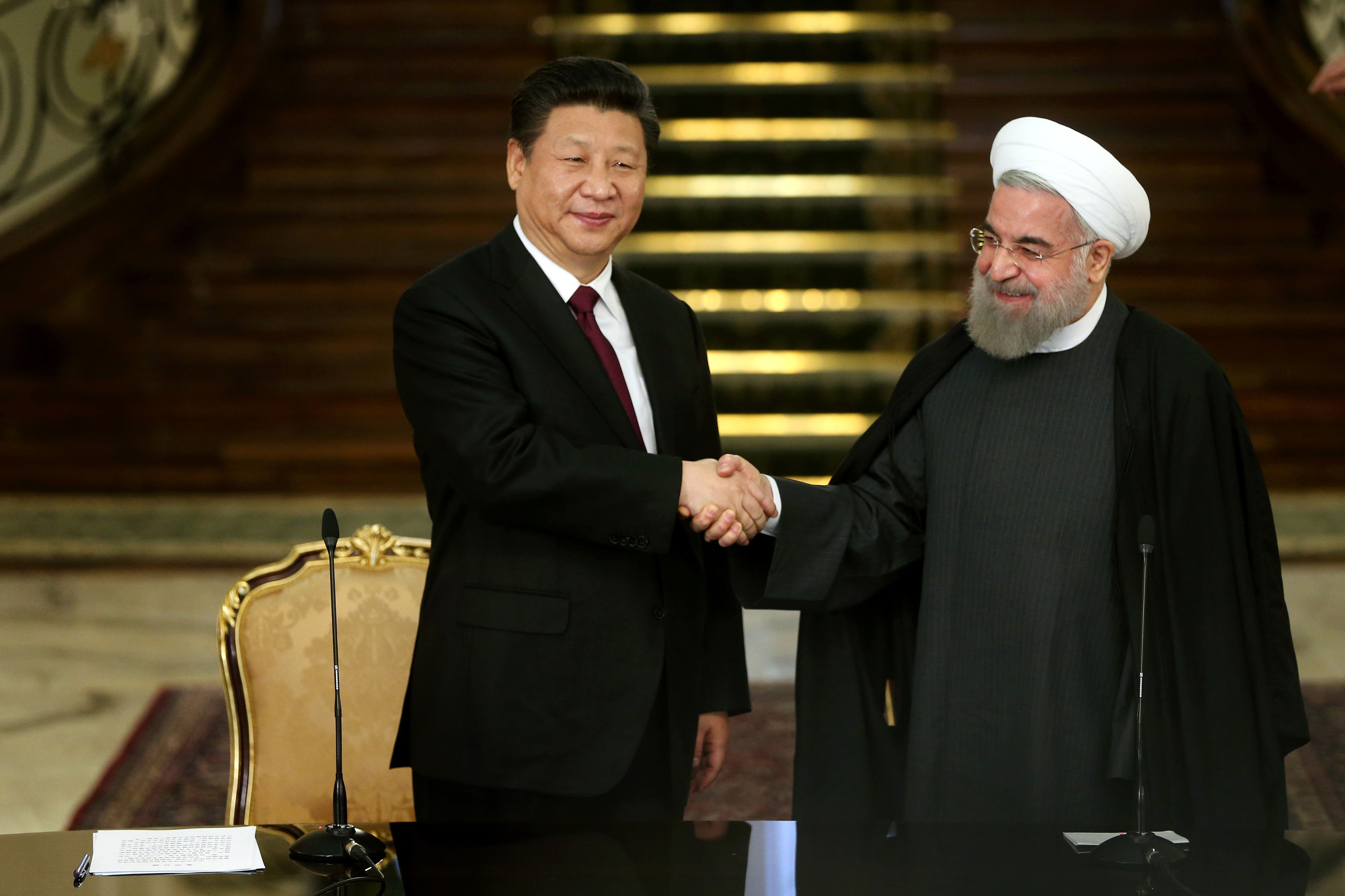Iranian President Hassan Rouhani, right, and his Chinese counterpart Xi Jinping shake hands at the conclusion of their joint press conference at the Saadabad Palace in Tehran, Iran, Saturday, Jan. 23, 2016