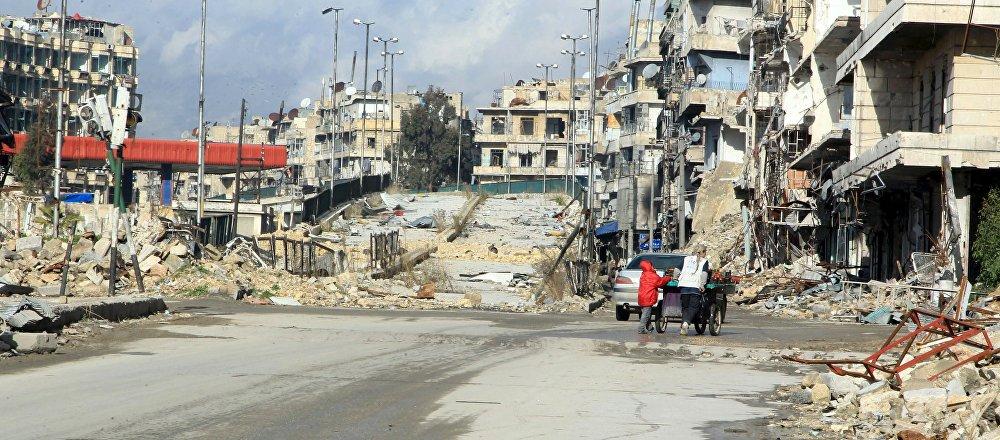 Residents push a cart near al-Shaar bridge in Aleppo's al-Shaar neighborhood, Syria, January 19, 2016