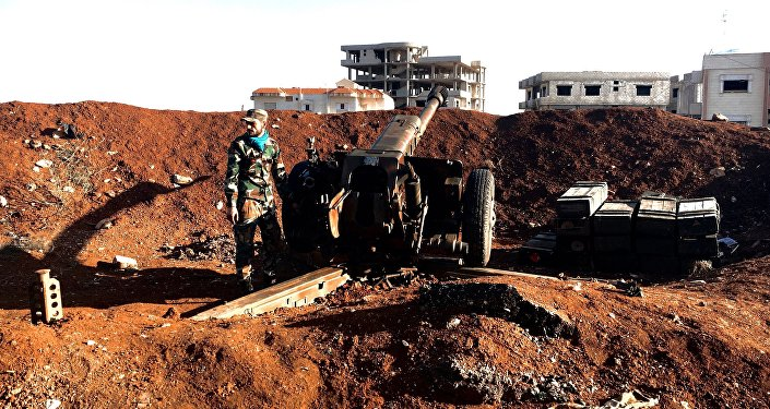 A soldier of the Syrian army stands by a gun during an assault on the town of Osman in Syria's province of Daraa