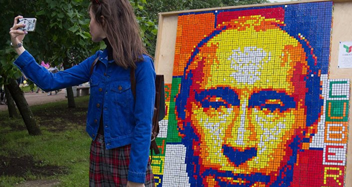 A girl takes a selfie against a portrait of Russian President Vladimir Putin composed of Rubik's Cubes at the festival of the social network VKontakte in St. Petersburg
