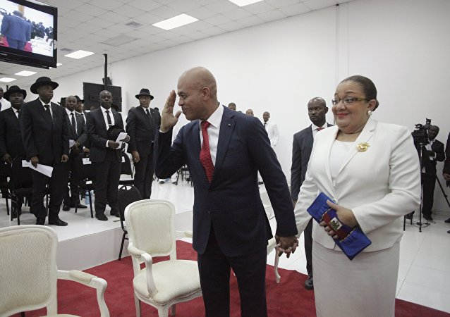 Haiti's former President Michel Martelly says goodbye as he accompanied by his wife Sophia at the end of a ceremony marking the end of his presidential term in the Haitian Parliament in Port-au-Prince, Haiti, February 7, 2016