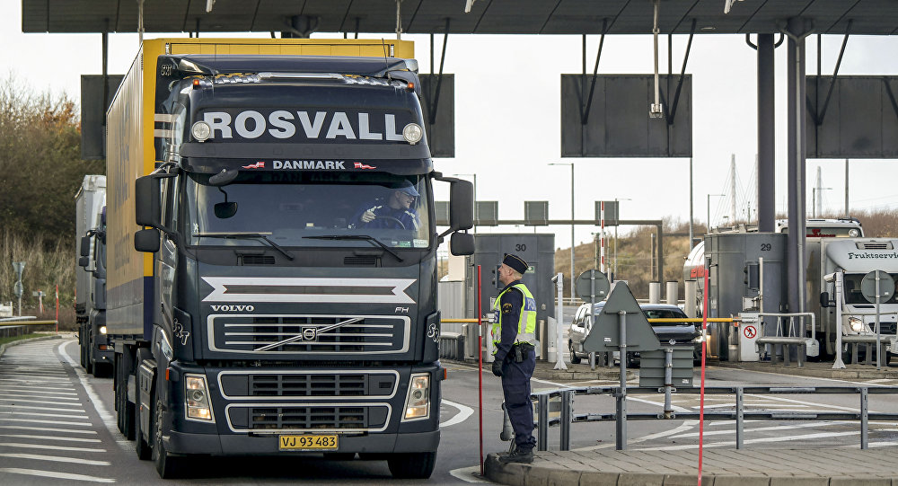 Police and customs personnel stop a freight truck at the toll booth at the Swedish end of the bridge between Sweden and Denmark in Malmo, Sweden