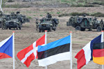 In this June 18, 2015,file photo flags wave in front of soldiers who take positions with their army vehicles during the NATO Noble Jump exercise on a training range near Swietoszow Zagan, Poland