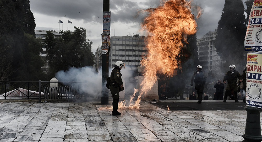 A firebomb explodes beside a riot police member during a massive protest in Athens on February 4, 2016.