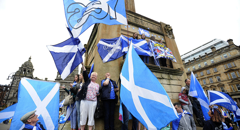 Pro-independence supporters wave the Scottish flag during a rally in George Square in Glasgow, Scotland, on 19 September 2015.