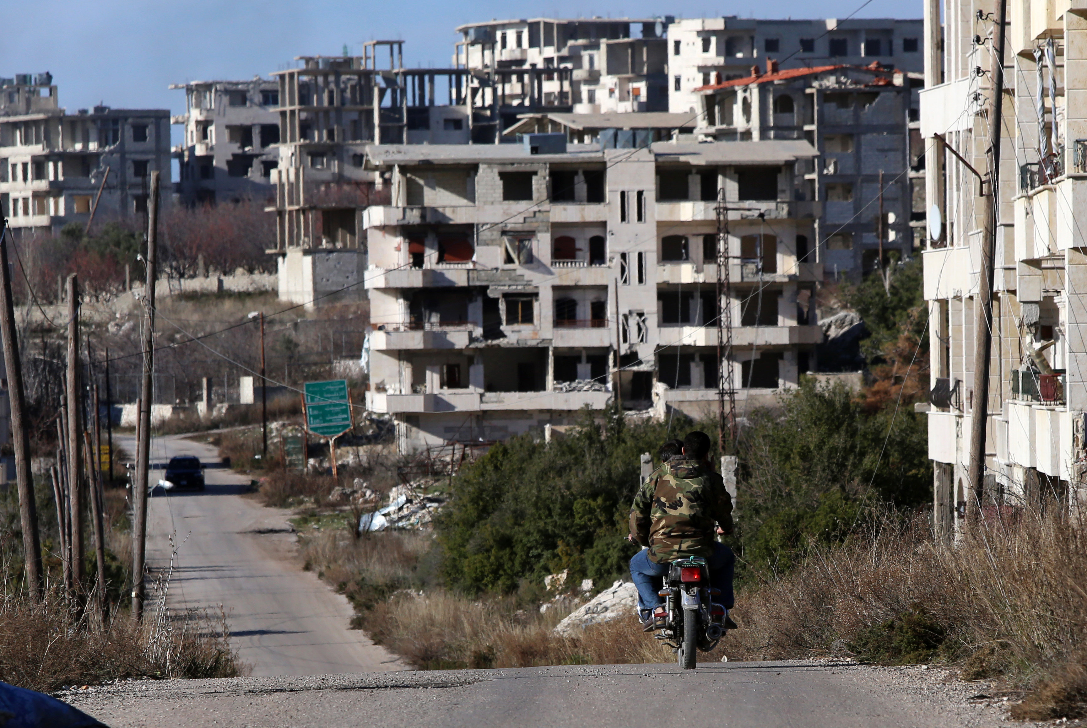Syrian army soldiers ride a motorcycle in the village of Salma, in the northwestern province of Latakia on January 15, 2016