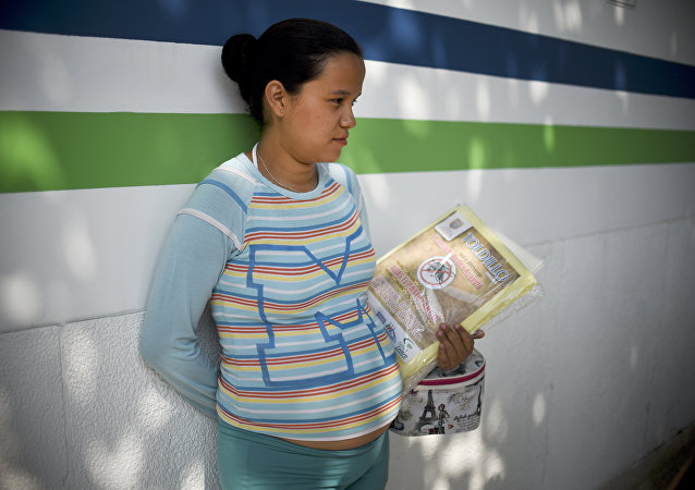 A pregnant woman holds a mosquito net in Cali