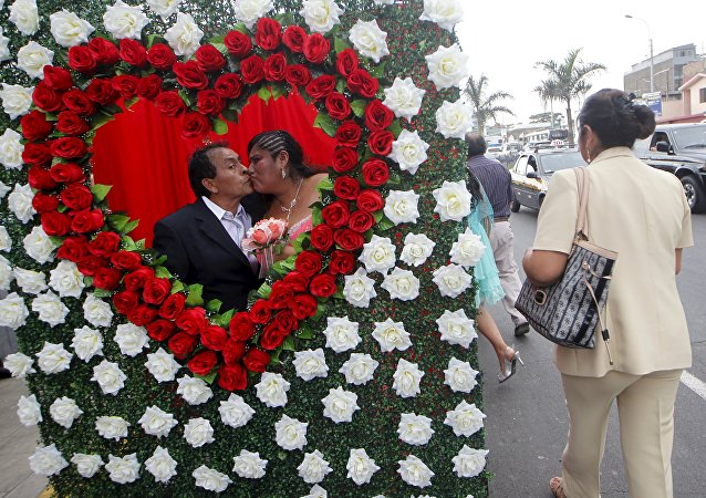 A couple kiss while posing for a picture after a mass wedding ceremony ahead of Valentine's Day celebration in Lima, Peru