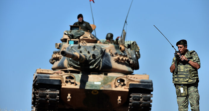 An officer speaks on the radio as Turkish tanks line up on a hill outside on the Turkish-Syrian border (file photo)