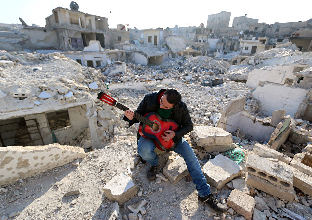 Shehab, a 23-year-old Syrian, practices the guitar amidst the rubble of buildings in the northern Syrian city of Aleppo on December 11, 2015.