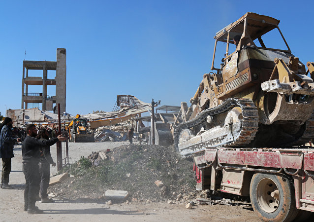A bulldozer is unloaded from a truck as people gather around the rubble of a hospital supported by Doctors Without Borders (MSF) near Maaret al-Numan, in Syria's northern province of Idlib, on February 15, 2016
