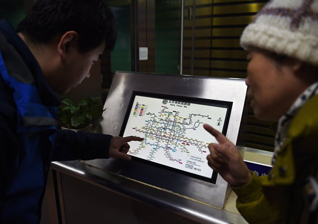 An attendant (L) explains details of new charges to a commuter in front of a subway map at a subway station in Beijing on December 29, 2014
