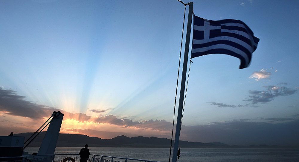 A man watches the sunrise from a ferry near the port of Piraeus on April 23, 2014.
