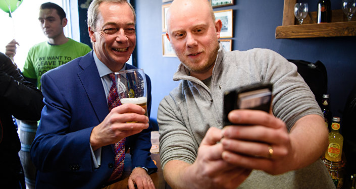 UK Independence Party (UKIP) leader Nigel Farage (L) poses for a selfie with Martin Clarke, owner of The Little Ale House, in Wellingborough, UK.
