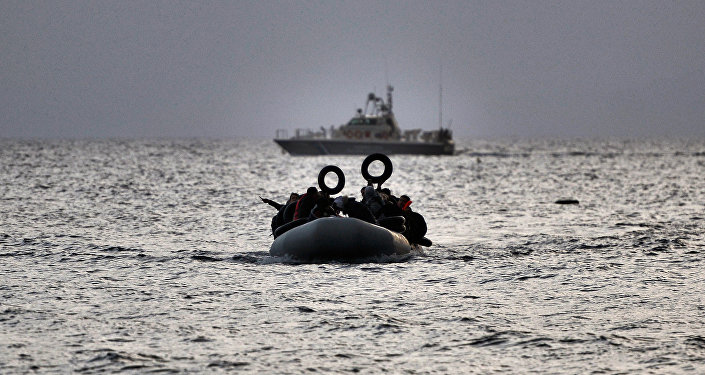 Refugees and migrants on a dinghy approach Mytilene on the northern island of Lesbos after crossing the Aegean sea from Turkey on February 19, 2016