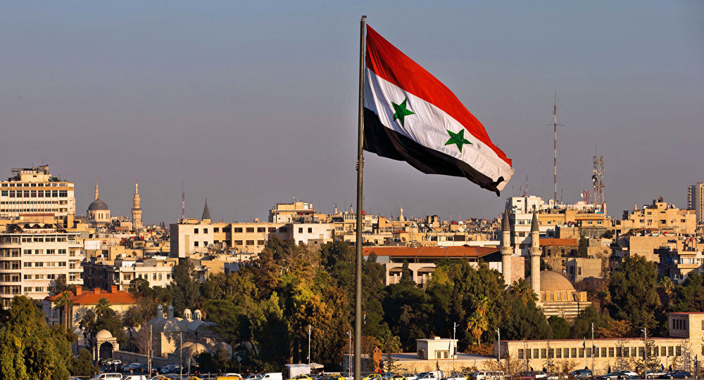 A Syrian national flag waves as vehicles move slowly on a bridge during rush hour, in Damascus, Syria, Sunday, Feb. 28, 2016