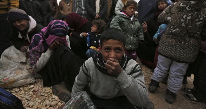 Syrians gather at the Bab al-Salam border gate with Turkey, in Syria, Saturday, Feb. 6, 2016