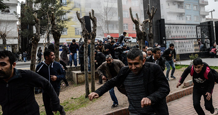 People disperse as Turkish police fire tear gas in Diyarbakir on February 27, 2016 during a demonstration against government-imposed curfews on areas of eastern Turkey