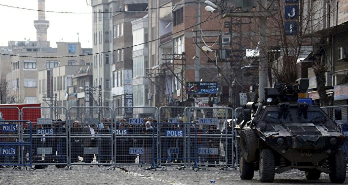 People stand behind the security barriers at one of the entrance of Sur district, which is partially under curfew, in the Kurdish-dominated southeastern city of Diyarbakir, Turkey February 26, 2016
